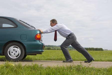 Empresario empujando un coche con el depósito de combustible vacío  Foto de archivo