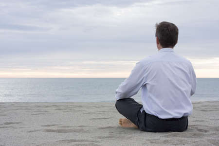 Businessman meditating on a beach at the sea