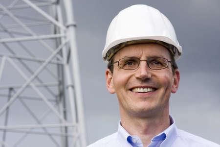 工事現場でヘルメットと笑みを浮かべてエンジニア