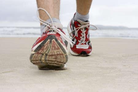 Pies de hombre con las zapatillas para correr en una playa