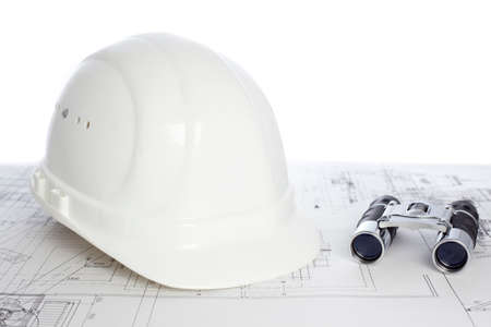 Hard hat and binoculars lying on construction plan - white background