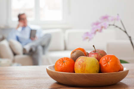 Fruit bowl on a table and man working with smartphone in the background