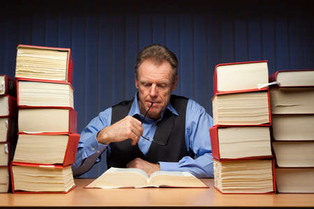 Mature lawyer or businessman reading at a desk in a dark office late at night