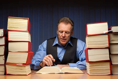 Mature lawyer, judge or office worker reading at a desk with many books late in the evening or at night