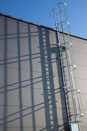 Fire escape or rescue ladder at a modern industrial building with shadows on the wall Banque d'images - 143532046