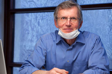 Portrait of a friendly smiling doctor at his desk wearing a surgical mask - focus on the face Фото со стока