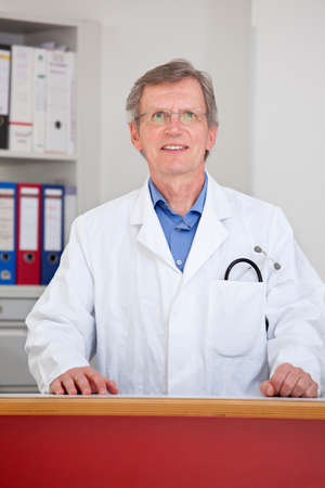 Mature smiling doctor standing behind the counter of his office - focus on the face