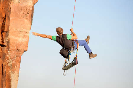Rock climber and photographer Norbert Frank ascending a rock with a rope Foto de archivo