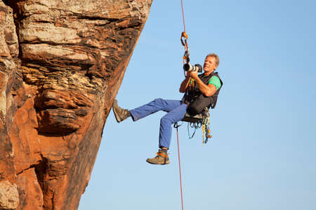 Photographer and rock climber Norbert Frank taking pictures in while hanging in front of a rock