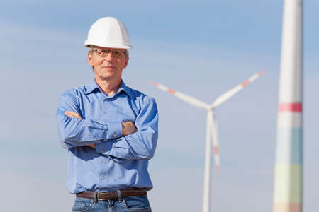 Smiling engineer with hard hat in front of a windmill - focus on the person