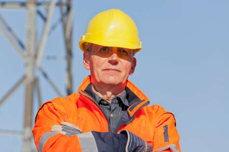 Portrait of a confident engineer, foreman or worker with protective clothing an hard hat in front of industrial background with blue sky Banco de Imagens