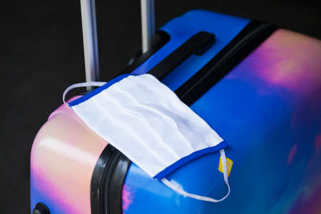 Face mask lying on a suitcase at an airport - focus on the hand Stock Photo