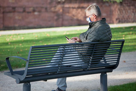 Mature man with face mask looking at a mobile phone while sitting on a park bench - selective focus on the head and hand Imagens