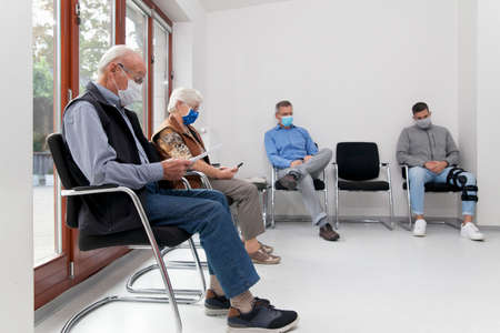 Senior couple with face masks sitting in a waiting room of a hospital together with a young and mature man - focus on the old man in the foreground