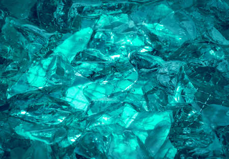 Gentle teal fond of sparkling water-washed grained rock with jagged edges, mysteriously lit сerulean сeleste сyan glow. Closeup view with space for text