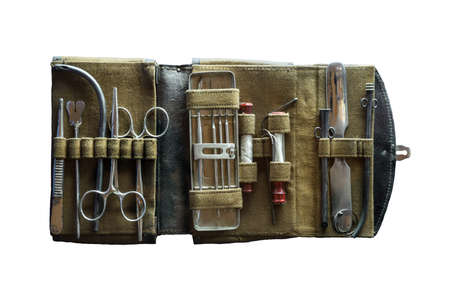 Aged nurse physician accessory in container on blue background. Aseptic hemostat, hypodermic tube, extraction tenaculum, steel hand lancet, tooth probe device, iron forcipes. Closeup obsolete object