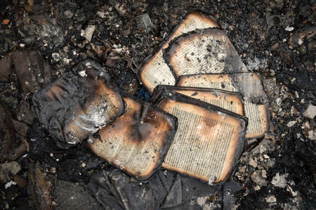 Uneven tattered wrinkled book with text in Russian language on pile of garbage after decay char scorch fiery in old house. Top view of littered with charred household items surface Reklamní fotografie
