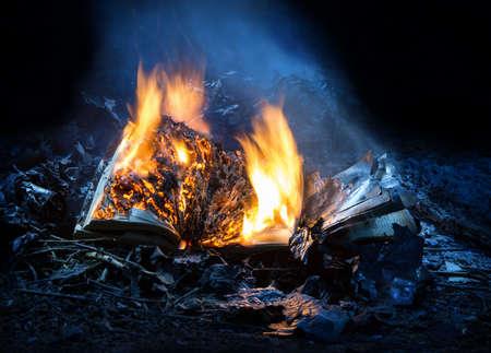 Verbrennen Sie glänzendes loderndes gealtertes offenes antikes Buch auf schwelendem Reisig in der blauen Nacht. Nahaufnahmemakroansicht mit Platz für Text auf schwarzem Hintergrund