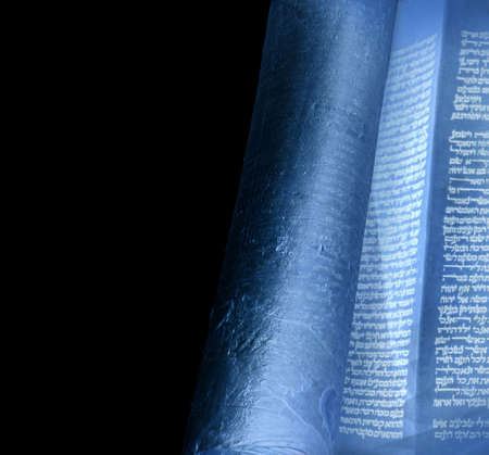 Open old sacred Jewry Tanakh law document bar mitzvah on synagogue alter, hand written on skin vellum in judaica language by scribe by quill and ink. View close-up isolated on dark black backdrop Stock Photo