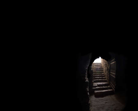 Arc fort passageway from cold damp Blackness to glow Light with rusted iron grate cell. Gaol rugged ominous shadow solid hallway with upward leading to day sunlight with space for text on sky backdrop 免版税图像