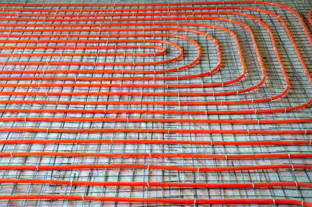 Modern manual laying of tuning water hydronic gas firing conduit supply on metal mesh insulation indoor new house room. Ground repair texture. Detail closeup macro view with space for text on grey net