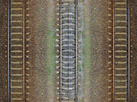 Seamless railroad Pattern backdrop with space for text. Top view. Shiny iron rails and concrete sleepers coupled with powerful bolts on stony ground fortified rubble overgrown with weeds green
