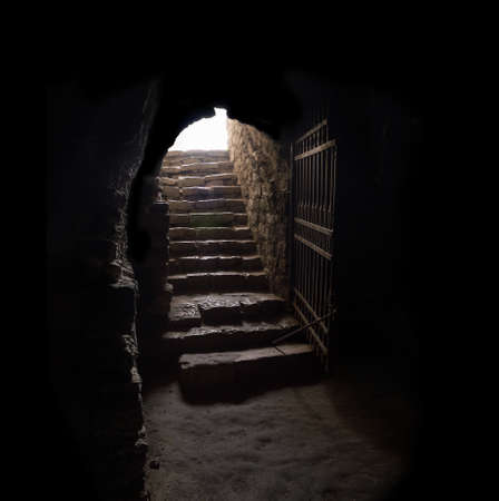 Arc fort passageway from cold damp Blackness to glow Light with rusted iron grate cell. Gaol rugged ominous shadow solid hallway with upward leading to day sunlight with space for text on sky backdrop Stock Photo