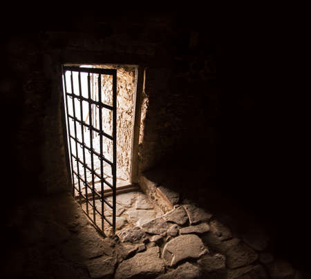 Arc fort passageway from cold damp Blackness to glow Light with rusted iron grate cell. Goal rugged ominous shadow solid hallway with upward leading to day sunlight with space for text on sky backdrop
