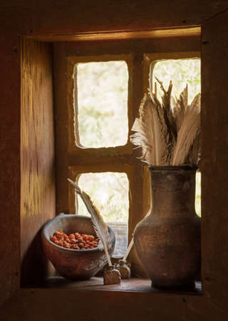 Antiquity scribe still life with goose pen in jar for write and dry ashberry in clay cup on wooden windowsill at dark hut. Closeup view with space for text in white glowing frame with glass background