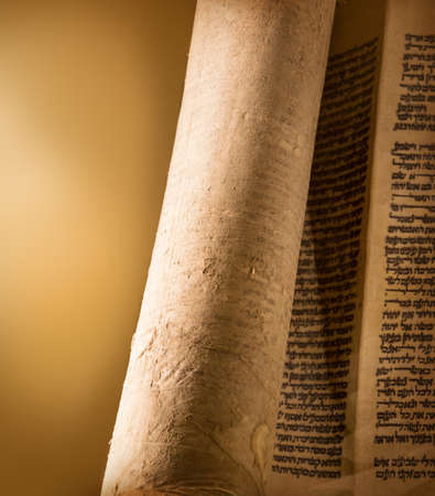 Оpen old sacred Jewry Tanakh law document bar mitzvah on synagogue alter, hand written on skin vellum in judaica language by scribe by quill and ink. View close-up isolated on dark ocher backdrop Stock Photo