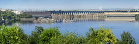 Zaporozhye, 2015 july 9. Dneproges - largest hydrostation PSP, pumped storage plant line on Dnipro. Summer panoramic view from island Hortitsa with space for text on blue sky