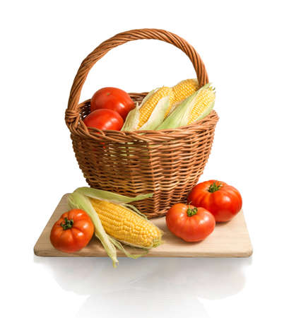 Vegan home kitchen still life of healthy diet products. Ripe golden corn cobs and large red salad tomatoes in old wicker basket on chopping wooden board isolated on white backdrop with clipping mask Stock Photo