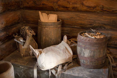Grungy aged country style storage used oak tun barel, worn horse seat, supply items making store on dusty chest in board shed. Closeup view with space for text on dark brown bar wall cottage backdrop  Reklamní fotografie