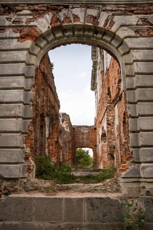 Aged luxury gloomy tunnel hole with large dark grey arc in deserted home of philanthropist Mikhail Tereshchenko destroyed by war. Zhytomyr, Ukraine, Europe. Front view with space for text on white sky