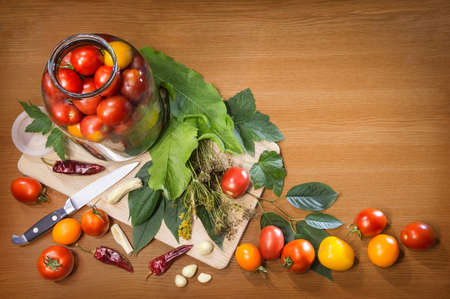 Different varieties of fresh ripe tomatoes arranged in glass jar, knife, leaves, tufts of dry fennel seeds, cloves of garlic, hot pepper isolated on wooden table with space for text. Top view close-up Reklamní fotografie