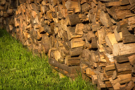 Picturesque old yellow billets stacked high logstack wall loaded on green grass lit by bright evening summer warm sun. View close-up with space for text on garden lawn