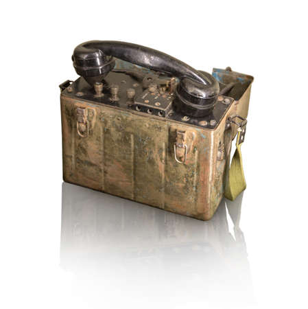 Vintage wartime period used soldier talk field case portable rusty shortwave node data demodulator box with plastic tube isolated on light backdrop with clipping path. View closeup with space for text