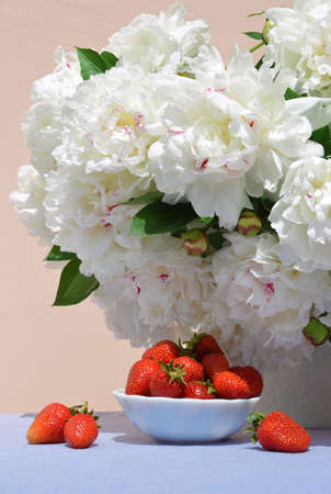 Vivid red juicy sweet strawberries in saucer on the background of a lush bouquet of peonies in delicate white vase with space for text on blue tablecloth