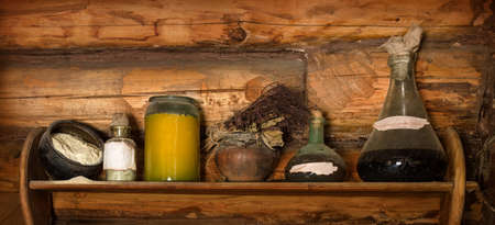 Grunge storage cupboard in hut with corked ink vial, poison phial, dry herb bunch, oil, scattered flour, jam and liqueur in jug with label for title. Closeup view with space for text on brown bar wall