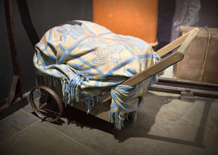 Rough big aged gone hand carry wagon wain lift pile of household items, covered an eldest tattered decorative patterned blanket. View closeup with space for text on night bygone train station backdrop