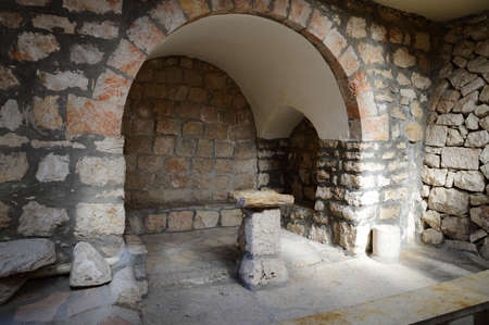 Aged orthodox indoor cellar touristic view. Vintage rock roman stand for preacher teach. Middle east place of crucifixion death, burial cave, resurrection of savior Jesus. Famous sacred historic scene