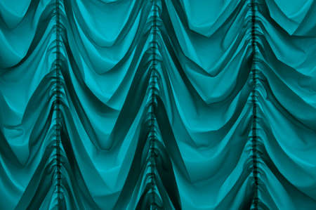 Trendy old fashioned repeating baroque soft satiny wrinkled blinds velum dark teal color with vertical plications. Romantic ancient royalty silky veil sheet design in retro style. Close up view space