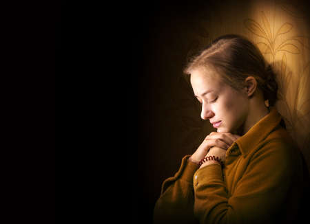 Dramatic evangelical pentecostal pious mourn pretty young light white lady kneeling ask implore wish upwards Jesus Christ. Vintage think life concept copyspace with space for text on dark backdrop Standard-Bild