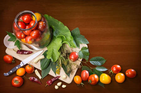 Different varieties of fresh ripe tomatoes arranged in glass jar, knife, leaves, tufts of dry fennel seeds, cloves of garlic, hot pepper isolated on wooden table with space for text. Top view close-up Stock fotó