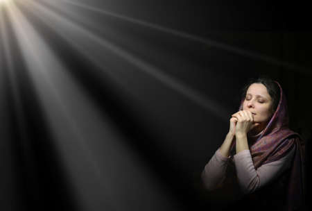 Dramatic evangelical pentecostal pious kneeling grieve young white lady cover head for ask implore wish upwards Jesus Christ. Vintage repentance concept copyspace with space for text on dark backdrop