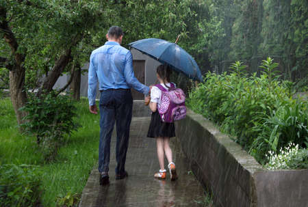 Cute 2 happy young adult coupl good safe relation little bag learn donate save hide under wet drop fall water symbol scen. Spring day baby outside urban town street yard garden nature scenic rear view 免版税图像