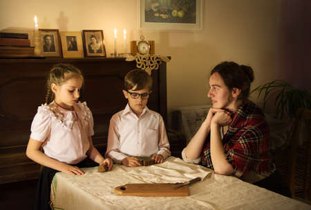 Cute tired female mum look worry face offer loaf receive hope aid life help. Little needy pauper baby charity 1930s concept. Old retro home room table great hardship recess dine dearth grief concern
