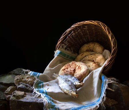 Holy fresh raw simple rural box barley pita cake bakery Lord pray bless retro Israel sign story. Close up view white jew towel cloth catch catholic supper still life dark black stone field text space 免版税图像