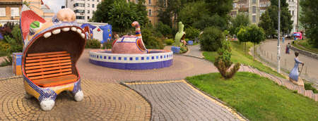 KYIV, UKRAINE 2018. Cute urban culture tree yard trip place panoram scene view. Chair sit funny joy prince boy pet toy open lip teeth known fairy tale Alice Pejzazhna avenue modern fun dream art style