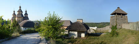 Khortitsa city 2018. Fortified rustic Zaporizhian Sich Hortica land white clay straw roof town guard army Museum. retro past age centurie peasant wood yard garden wall scene view blue Dnipro river sky Éditoriale